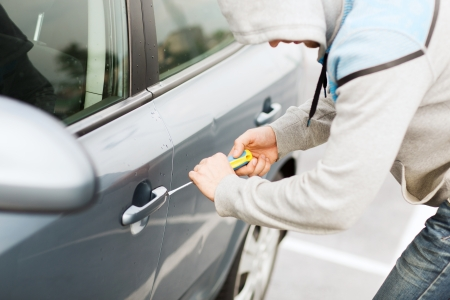 transportation, crime and ownership concept - thief breaking the car lock photo