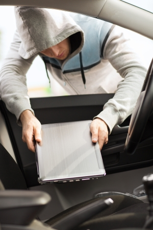 transportation, crime and ownership concept - thief stealing laptop from the car photo