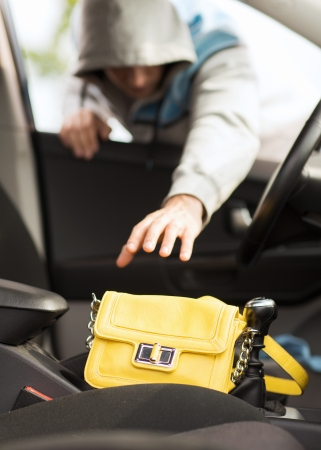 transportation, crime and ownership concept - thief stealing bag from the car photo