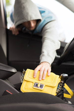 transportation, crime and ownership concept - thief stealing bag from the car Stock Photo