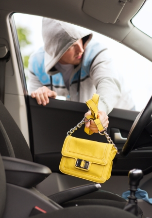 robbery: transportation, crime and ownership concept - thief stealing bag from the car Stock Photo