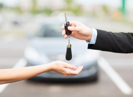 transport en eigenaarschap concept - klant en verkoper met autosleutel buiten