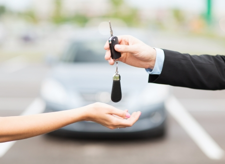 Driving: transportation and ownership concept - customer and salesman with car key outside