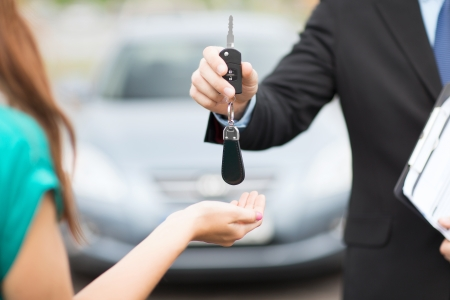 car loan: transportation and ownership concept - customer and salesman with car key outside