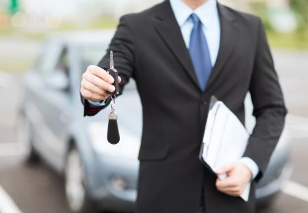 transport en eigenaarschap concept - man met autosleutel buiten