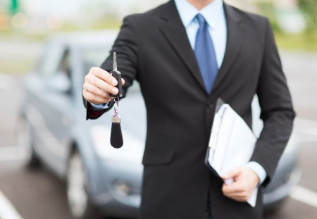 Leasing: transportation and ownership concept - man with car key outside