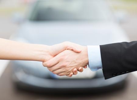 vervoer, bedrijven, winkels en eigendom concept - klant en verkoper handen schudden buiten
