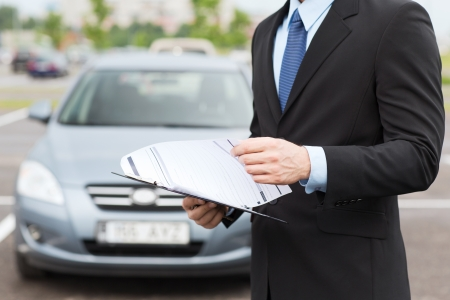 auto leasing: transportation and ownership concept - man with car documents outside