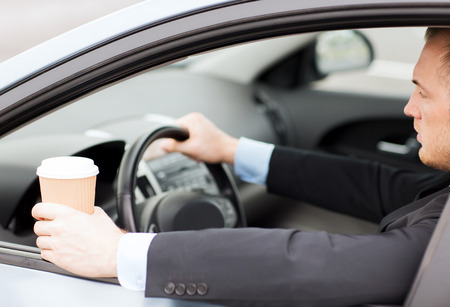 transportation and vehicle concept - man drinking coffee while driving the car Stock Photo - 22185119
