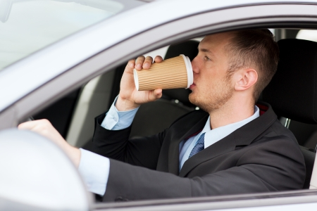 drinking and driving: transportation and vehicle concept - man drinking coffee while driving the car