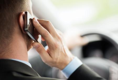 transport en concept voertuig - man met behulp van telefoon tijdens het rijden de auto Stockfoto