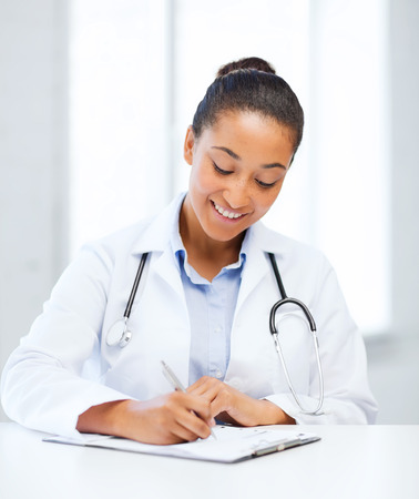 healthcare and medical concept - female doctor with stethoscope writing prescription photo