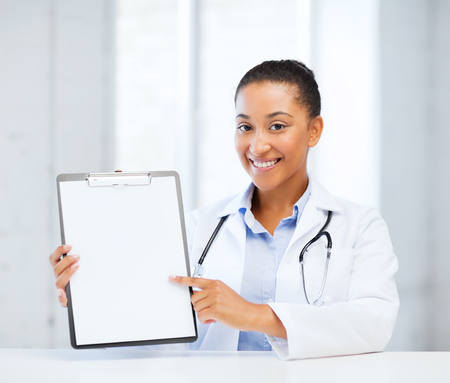 health care and medical concept - female doctor with stethoscope and blank prescription photo