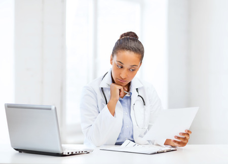 healthcare, medical and technology concept - african female doctor with laptop pc writing prescription photo