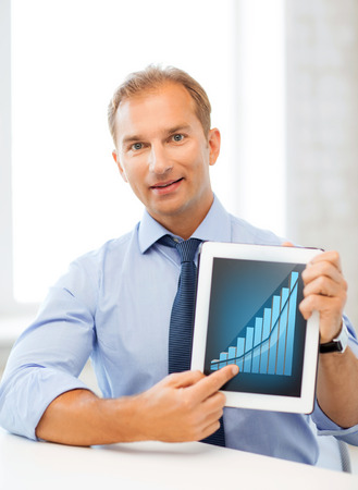 business and technology concept - businessman showing tablet pc with graph photo