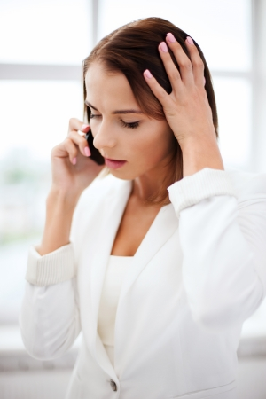 helpline: business concept - confused woman with smartphone in office