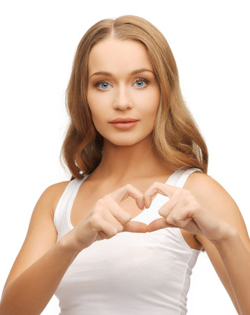health, charity - woman in white shirt showing heart shape with hands photo