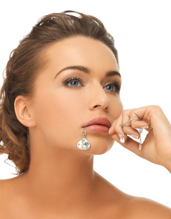 bride and wedding concept - beautiful woman holding shiny diamond pendant in mouth photo
