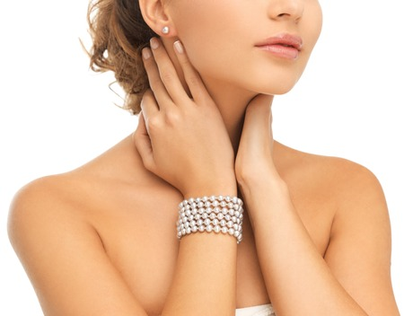 imitations: beauty and jewelery concept - beautiful woman with pearl earrings and bracelet