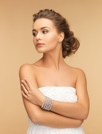 美容やジュエリー コンセプト - 真珠のイヤリングとブレスレットを持つ美しい女性 写真素材