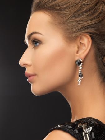 美しさとジュエリーのコンセプト - 女性の光沢のある身に着けているダイヤモンド イヤリング