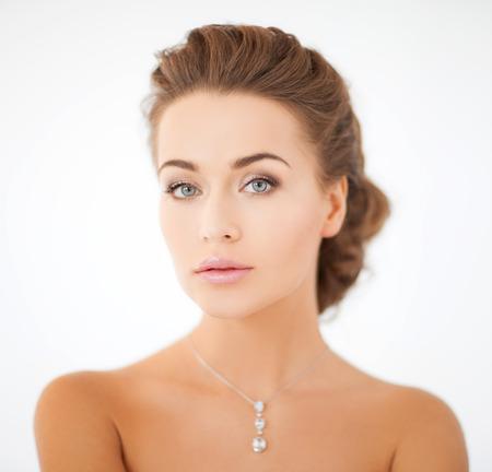 美しさとジュエリーのコンセプト - 光沢のある身に着けている女性のダイヤモンドのペンダント