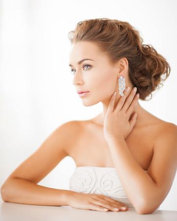 model nice: beauty and jewelery concept - woman wearing shiny diamond earrings Stock Photo