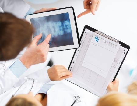 bone cancer: healthcare, hospital and medical concept - group of doctors looking at x-ray on tablet pc Stock Photo
