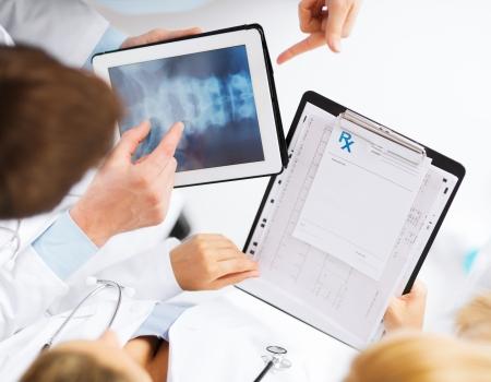 columna vertebral: salud, hospital y el concepto m�dico - grupo de m�dicos en busca de rayos x en el PC tableta