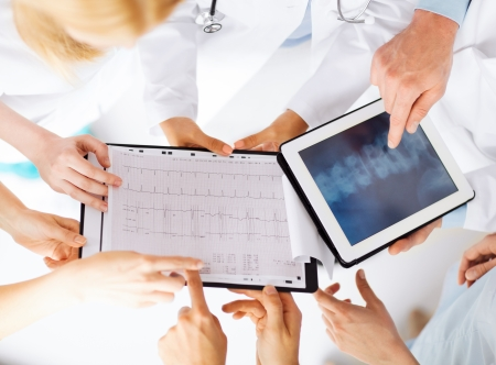 spine x ray: healthcare, hospital and medical concept - group of doctors looking at x-ray on tablet pc Stock Photo