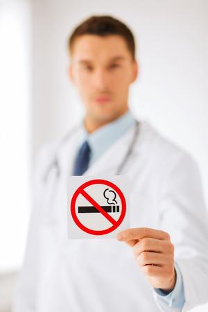 hombre fumando: la salud, la medicina y el concepto de Hospital - médico masculino sosteniendo señal de no fumar en las manos