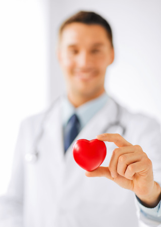 heart: healthcare and medical concept - male doctor with heart