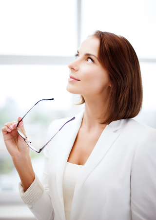 correction: business and vision correction concept - businesswoman with eyeglasses in office