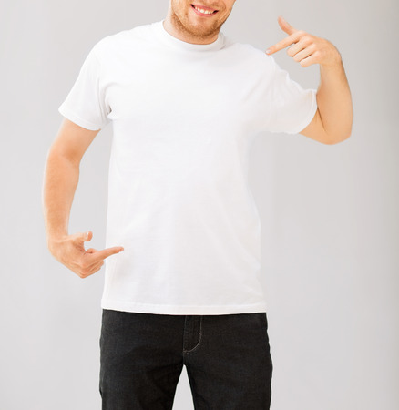 design and advertisement concept - picture of smiling man pointing at blank white t-shirt photo