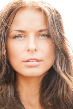 sensitive skin: health and beauty concept - face of beautiful woman with long hair