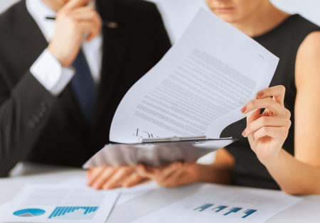 legal office: business, office, law and legal concept - picture of man and woman hand signing contract paper