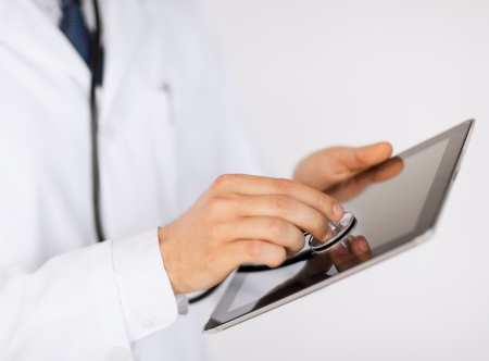 medicine, health and hospital concept - close up of male doctor with stethoscope and tablet pc photo