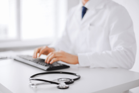 healthcare, hospital and medicine concept - male doctor typing on the keyboard photo