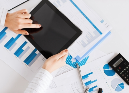 cashflow: business, office, school and education concept - woman with tablet pc and chart papers Stock Photo