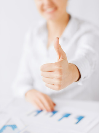 business, office, school and education concept - happy woman with charts, papers and thumbs up photo