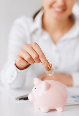 ビジネス、オフィス、家庭、学校、税金、教育概念 - 小さな貯金箱にコインを入れて女性手