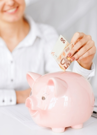 business, office, household, school, tax and education concept - woman puts euro cash into large piggy bank photo