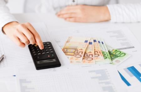 電卓: ビジネス、オフィス、家庭、学校、税金、教育概念 - 電卓とユーロのお金と女性手 写真素材