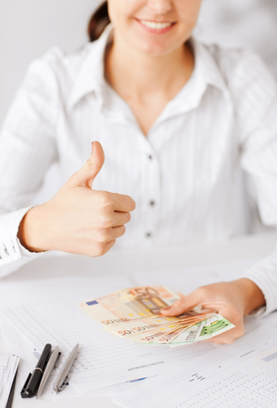 household money: business, office, household, banking, tax, gambling concept - woman hands with euro cash money and thumbs up