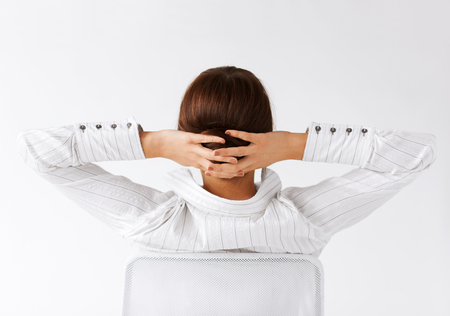 arm chair: business, office, school and education concept - relaxed woman from the back with arms on head