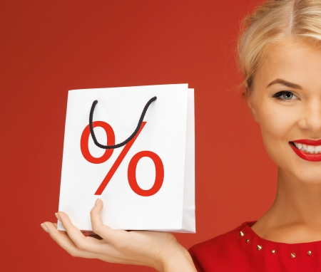 woman holding bag: holidays, sale, christmas and shopping concept - woman holding bag with percent sign