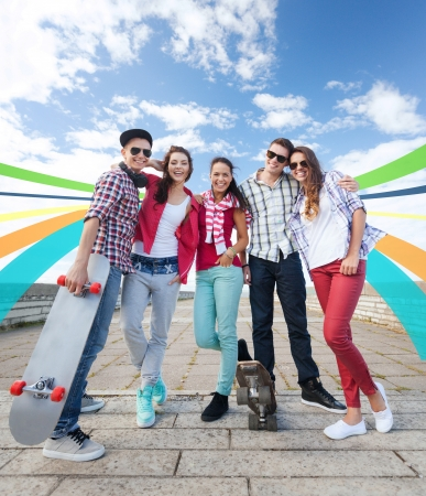 mates: summer holidays and teenage concept - group of teenagers with skates outside Stock Photo