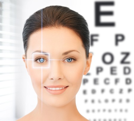eyes contact: future technology, medicine and vision concept - woman and eye chart Stock Photo