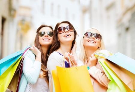 Compras y concepto de turismo - hermosas chicas con bolsas de la compra en ctiy Foto de archivo - 22380424