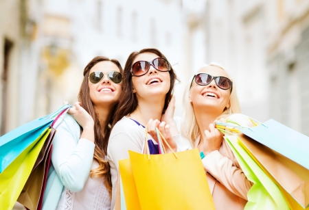 happy shopping: shopping and tourism concept - beautiful girls with shopping bags in ctiy